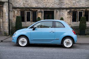 Niebieski samochód miejski Fiat 500 na tle ściany